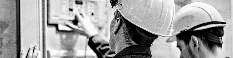 two men in hard hats looking away from the camera